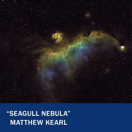 """A green, yellow and blue nebula in the shape of a bird in space with the text """"Seagull Nebula"""" Matthew Kearl"""