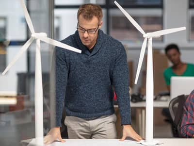 Man with glasses standing between models of wind turbines looking at engineering plans.