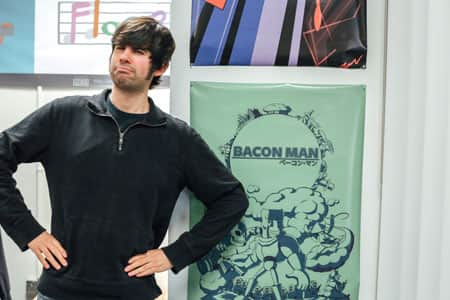Neal Laurenza posing next to a poster for Bacon Man game