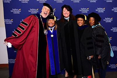 SNHU President Paul LeBlanc with 4 SNHU Graduates posing for a picture
