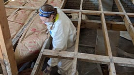 An SNHU community member at a house building site installing floor insulation