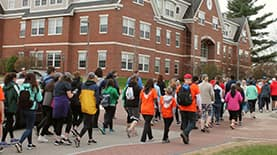 Large crowd of SNHU members walking outside on SNHU campus for a charitable cause