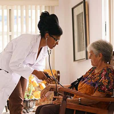 A nurse taking an elderly woman's blood pressure in the common room of an assisted living facility.