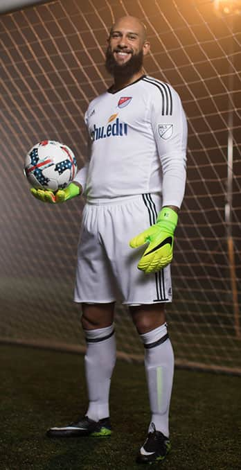 Tim Howard holding a soccer ball, wearing an SNHU jersey and standing in a soccer net.