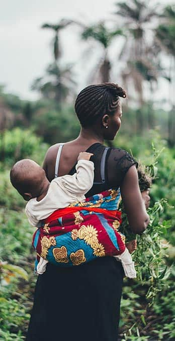 Woman carrying a baby on her back as she walks through fields