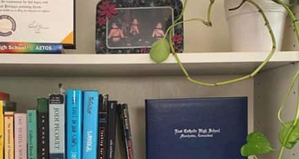 Books and a diploma on a book shelf