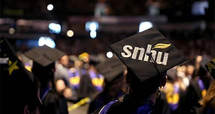Graduates at Commencement ceremony and a cap with the SNHU logo in the foreground
