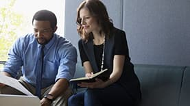 Man in blue shirt looking at business plan along with woman in  business suit.