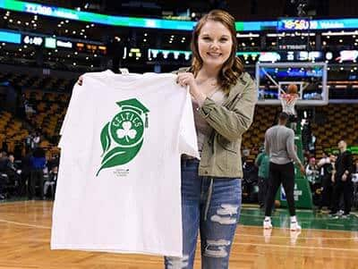 SNHU student Mary Shakshober standing on the court of the TD Garden holding the T-shirt she designed for SNHU Night.