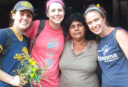Three SNHU students posing with a member of the community during volunteer work