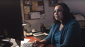Katrina Jagroop-Gomes at a desk on the computer as she earns her MBA