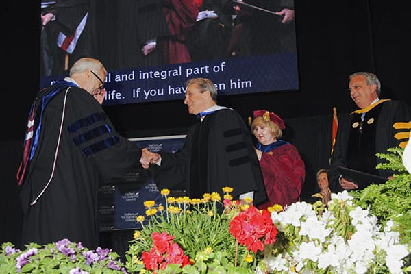 a student receiving diploma at Commencement 2014