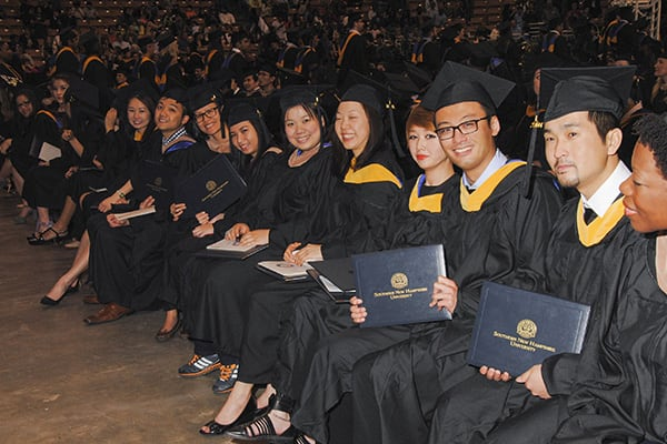 students sitting after receiving diplomas