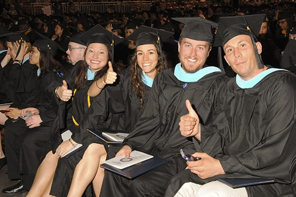 "a group of students giving a ""thumbs up"" at Commencement 2014"