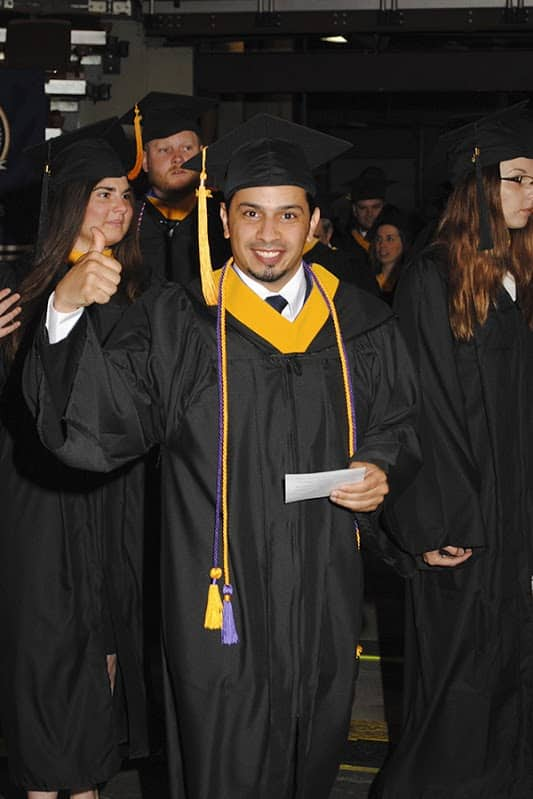 a student celebrating while walking at Commencement 2014