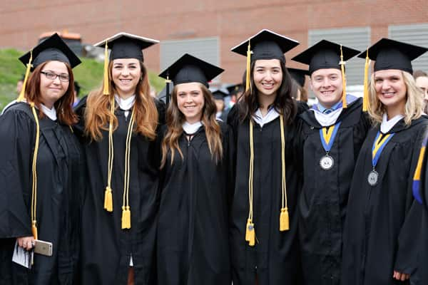 Students wearing caps and gowns at commencement 2015