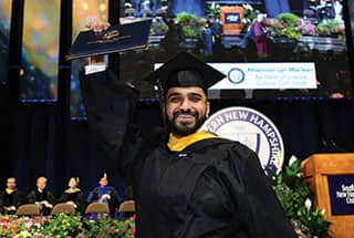 SNHU graduate holding up his diploma at the 2019 Commencement ceremony