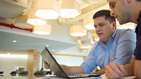 SNHU Online MBA student Kyle looking at a laptop with a colleague