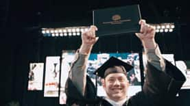 SNHU Graduate John holding up his diploma at Commencement