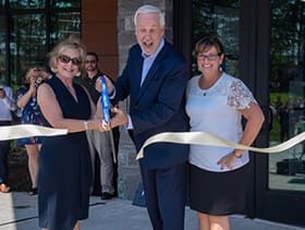 SNHU President Paul LeBlanc cutting a ribbon opening Kingston Hall with two women.