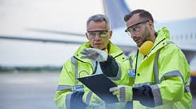 Two men in green safety jackets and gloves standing in front of an airplane consulting a clipboard.