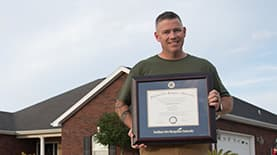 A photo of Jon Galvin holding his framed SNHU degree.