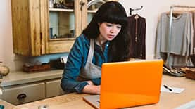 Woman researching fashion merchandising colleges online