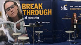 A womn sitting at a table at SNHU's booth at the Grace Hopper Celebration.