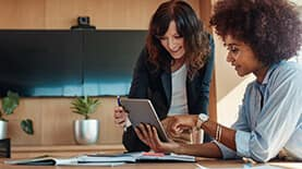 Woman in office setting pointing at a tablet while a second woman looks on.