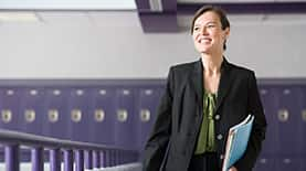 A woman with her M.Ed in a school hallway lined with purple lockers.
