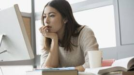 Photo of a woman staring intently at a computer monitor while search for scholarships online.