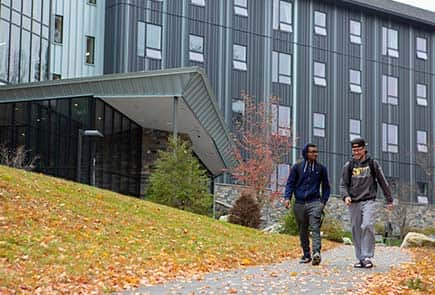two students walking in front of Residence Apartments on Campus