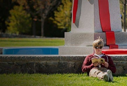 Person reading a book by a monument.