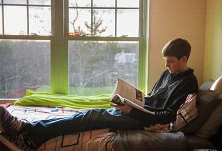 a SNHU student reading in their on campus townhouse