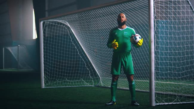MLS goalkeeper Tim Howard holds a soccer ball while standing in a goal.