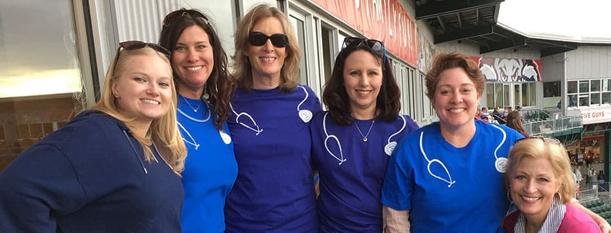 ​Group of nursing students and their academic advisors standing in the bleachers at a local baseball game​