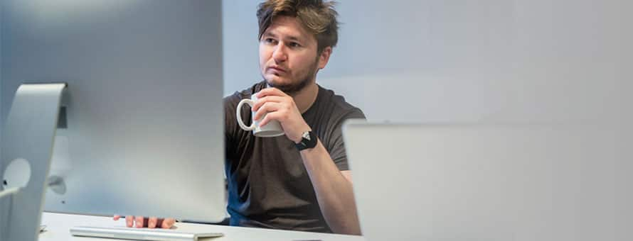 Man sitting at a desktop computer with a cup of coffee building his personal brand online​
