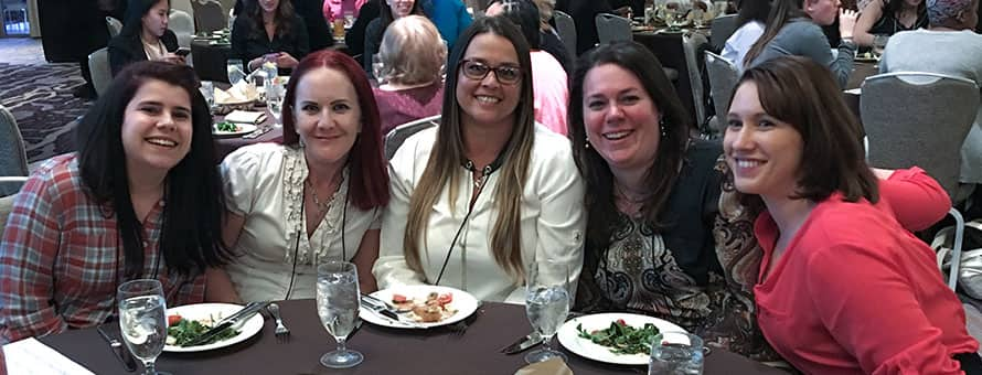 Five online students pursuing cybersecurity careers attending the Women in Cybersecurity conference
