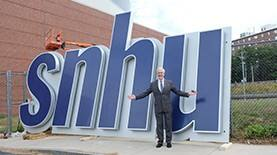 SNHU President Paul LeBlanc standing with new arena sign